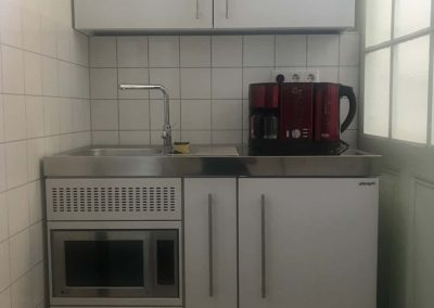 Küchennische mit Kaffemaschine, Kühlschrank und Mikrowellenofen